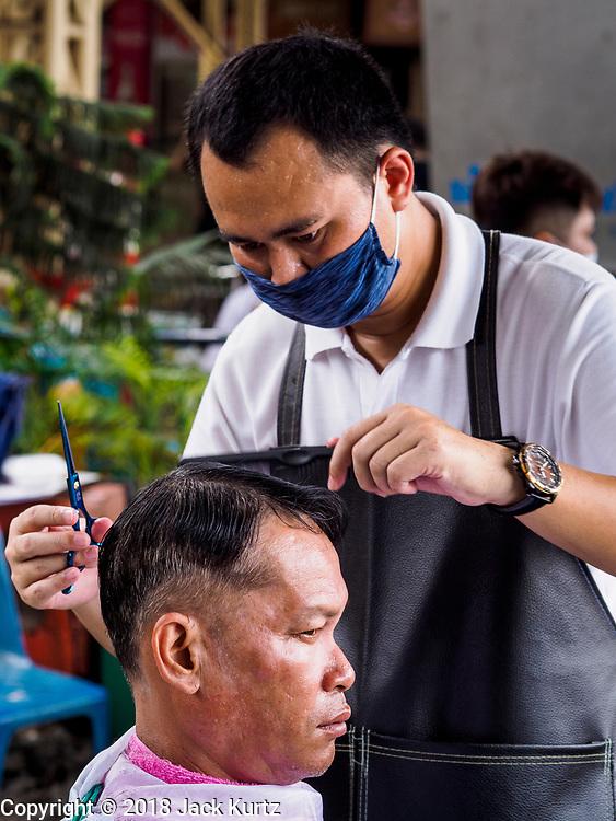 12 SEPTEMBER 2018 - BANGKOK, THAILAND: A barber gives a man a haircut at Hua Lamphong train station in Bangkok. Barber schools set up in the station and offer free haircuts to travelers.     PHOTO BY JACK KURTZ