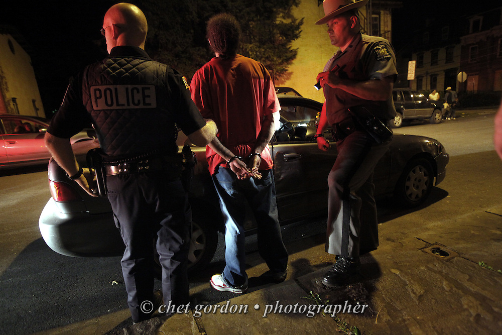 Newburgh police officer Billy Hinspeter (left) and State Police trooper Jason Grabowski (right) place an individual under arrest after a vehicle stop on Lander Street in the City of Newburgh, NY late Friday night, July 10, 2009. The passenger was taken into custody after it was determined he had an active warrant against him.