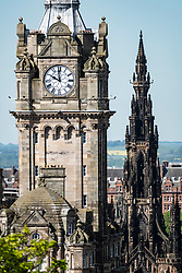View of clocktower on Balmoral Hotel and Scott Monument on Princes Street in Edinburgh, Scotland, UK.