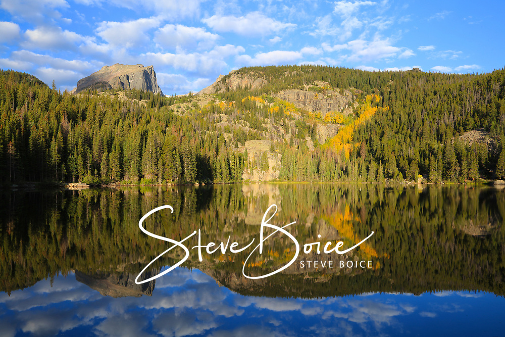 Changing aspen trees and Hallet Peak reflect in the calm water of Bear Lake in Rocky Mountain National Park, Colorado