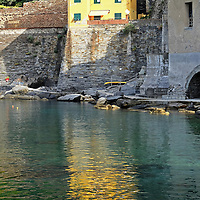 A yellow house in Vernazza, Italy is reflected on water