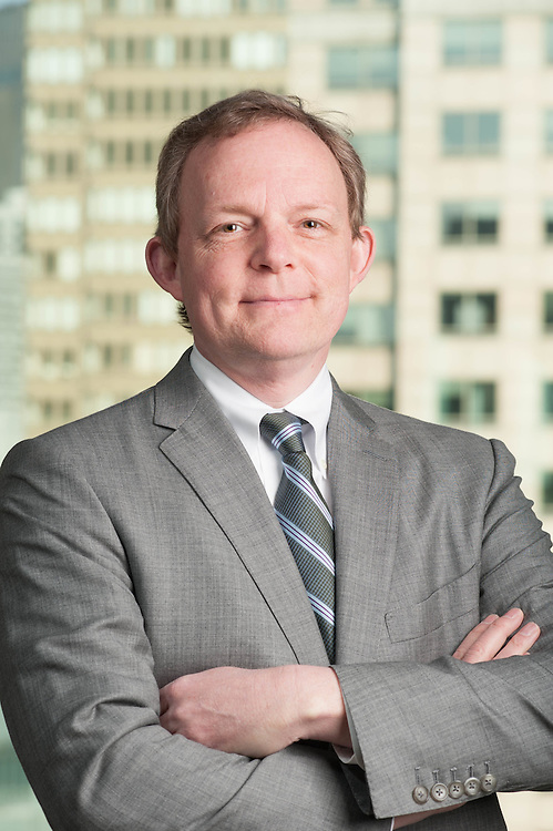 Executive headshot taken at his office with Boston serving as background.