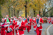The London Santa Run 2015 in Battersea Park - 2,000 Santa's take part in an annual 'Red & White' bearded 'charge' around Battersea Park in a 6k festive charity fun run. The runners are of all ages and abilities and many run at a very slow pace but enjoy the event and the cause. The Santa Run is organised to raise funds for Disability Snowsport UK, a national charity helping people with disabilities to access the thrill of snowsports. The charity ensures that children and adults, with a range of disabilities (including cerebral palsy, Down's syndrome,  visual impairment and autism), can access programs across the UK to enable them to make friends, improve their confidence and have fun through a sport which they would otherwise be excluded from.