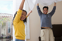 Mid-adult man and his daughter making a bed