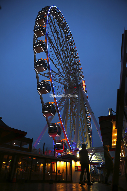 It's the calm before the storm at the Seattle Great Wheel, which saw a steady trickle of visitors under drizzly skies Mon. evening, Nov. 16, 2015, on Seattle's waterfront. More rains with high winds are expected to kick up Tuesday.