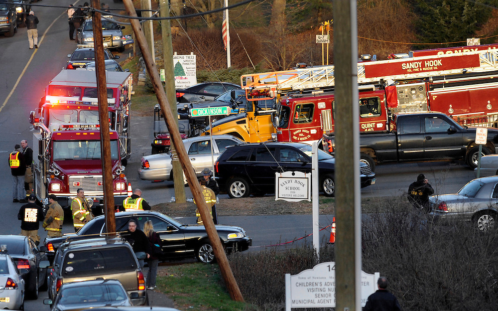 Emergency vehicles line the road at a firehouse staging area for family at the entrance to Sandy Hook School, the site of a school shooting in Newtown, Conn., Friday, Dec. 14, 2012. (AP Photo/Jessica Hill)