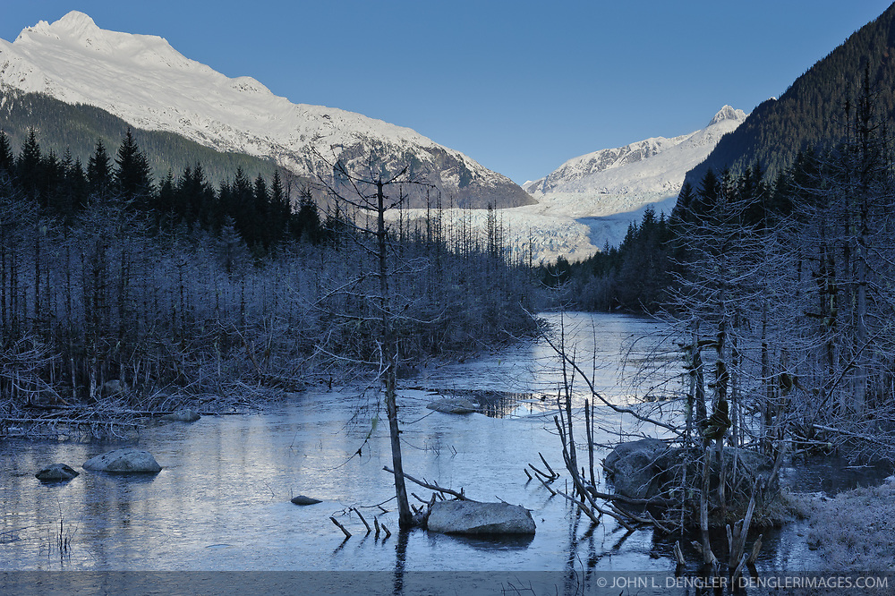 Steep Creek begins to freeze  near the Mendenhall Glacier (center). Mountain on the left is McGinnis Mountain. The Mendenhall Glacier runs roughly 12 miles, originating in the Juneau Icefield, near Juneau, Alaska. The glacier is located 12 miles from downtown Juneau.
