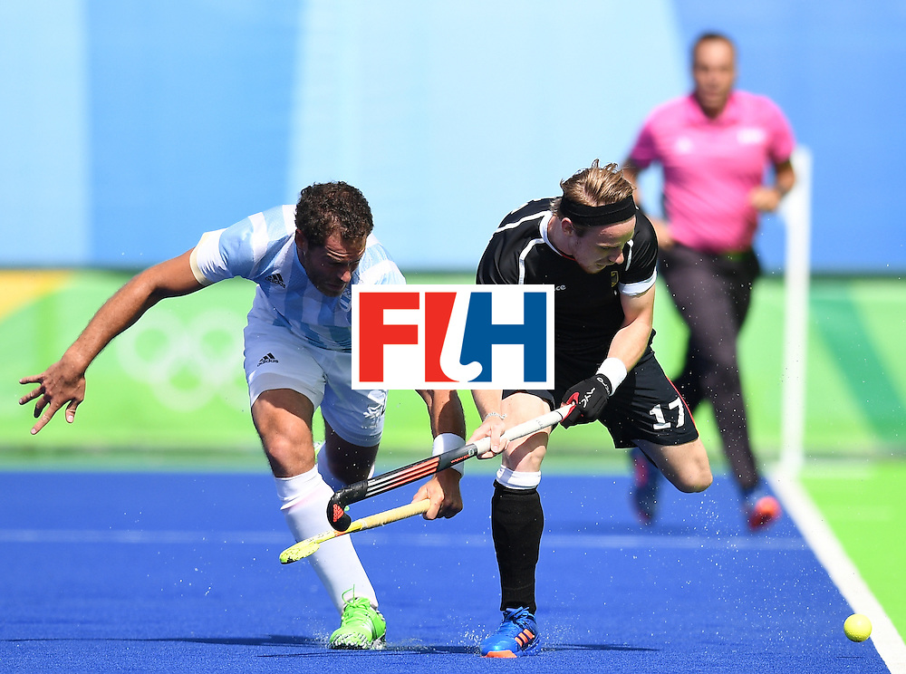 Germany's Christopher Ruhr (R) vies for the ball with Argentina's Juan Gilardi during the men's field hockey Argentina vs Germany match of the Rio 2016 Olympics Games at the Olympic Hockey Centre in Rio de Janeiro on August, 11 2016. / AFP / MANAN VATSYAYANA        (Photo credit should read MANAN VATSYAYANA/AFP/Getty Images)
