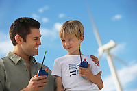 Father and son (7-9) holding toy walky-talkies at wind farm