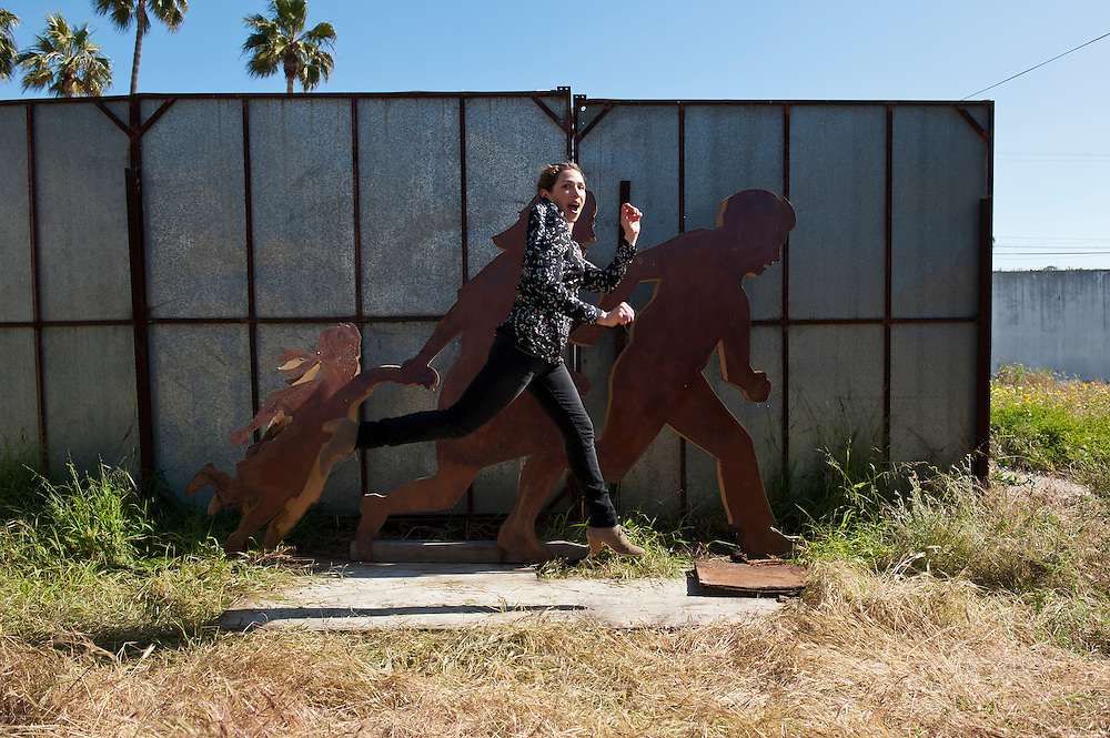 Artist Jean Von Borstel with her iron and wood sculpture in Playas Tijuana, Baja California, Mexico.<br /> <br /> &copy; Stefan Falke<br /> www.stefanfalke.com<br /> LA FRONTERA: Artists along the US Mexican Border