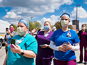 "06 MAY 2020 - DES MOINES, IOWA: Members of the nursing staff at Unity Point Health Iowa Methodist Medical Center in Des Moines, wave to passing police and fire vehicles as they drive past the hospital. Des Moines first responders, the Iowa State Patrol, and utility companies made an ""Appreciation Loop"" around the hospital on National Nurses' Day to thank nurses and other care givers at the hospital for the care they are providing during the COVID-19 (Coronavirus/SARS-CoV-2) pandemic. Iowa reported 10,404 confirmed cases of COVID-19 statewide Wednesday, about 2,500 cases in the Des Moines metropolitan area. Acting against the advice of many medical professionals, the Governor of Iowa has started reopening businesses in the state. Businesses in the Des Moines area, and other communities with a high number of cases are not allowed to reopen.       PHOTO BY JACK KURTZ"