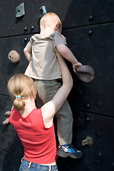Older sister helping her younger brother climb a climbing wall at the local park,