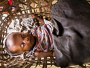 07 NOVEMBER 2014 - SITTWE, RAKHINE, MYANMAR: A Rohingya Muslim baby born in an IDP camp sleeps in a cradle made of palm fronds in a tent in an IDP camp near Sittwe. After sectarian violence devastated Rohingya communities and left hundreds of Rohingya dead in 2012, the government of Myanmar forced more than 140,000 Rohingya Muslims who used to live in and around Sittwe, Myanmar, into squalid Internal Displaced Persons camps. The government says the Rohingya are not Burmese citizens, that they are illegal immigrants from Bangladesh. The Bangladesh government says the Rohingya are Burmese and the Rohingya insist that they have lived in Burma for generations. The camps are about 20 minutes from Sittwe but the Rohingya who live in the camps are not allowed to leave without government permission. They are not allowed to work outside the camps, they are not allowed to go to Sittwe to use the hospital, go to school or do business. The camps have no electricity. Water is delivered through community wells. There are small schools funded by NOGs in the camps and a few private clinics but medical care is costly and not reliable.   PHOTO BY JACK KURTZ