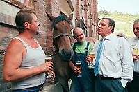 24 AUG 2000, NAUMBURG/GERMANY:<br /> Gerhard Schroeder, SPD, Bundeskanzler, trinkt - ausserhalb des Programms - ein Bier, mit einem Hufschmied, einen Kutscher, und dessen frisch beschlagenen Kaltblutpferd, auf einem Gehoeft in der Naehe von Naumburg, Sommerreise des Kanzlers durch die Ostdeutschen Bundeslaender<br /> IMAGE: 20000824-01/03-30<br /> KEYWORDS: Gerhard Schröder, Pferd, Tier, horse, animal, Hufeisen, Handwerk, Arbeit, work, beer, Alkohol, alcohol, Getraenk, drink