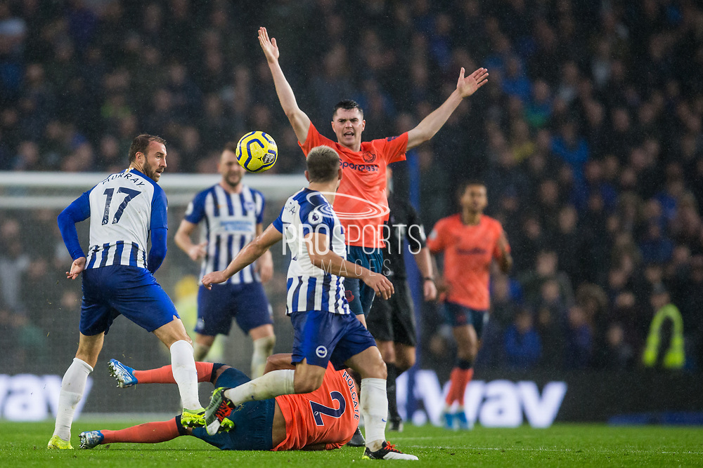 Michael Keane (Everton) protest as Mason Holgate (Everton) lands on the ground following a tackle with Glenn Murray (Brighton) close by during the Premier League match between Brighton and Hove Albion and Everton at the American Express Community Stadium, Brighton and Hove, England on 26 October 2019.