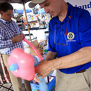 Jon Tait, left, and Joe Hagan makes baloon animals at the Lelan Area Rotary booth at the Leland Founder's Day festival.