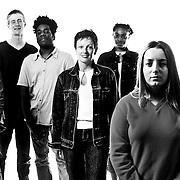Group of seven models stood looking at camera