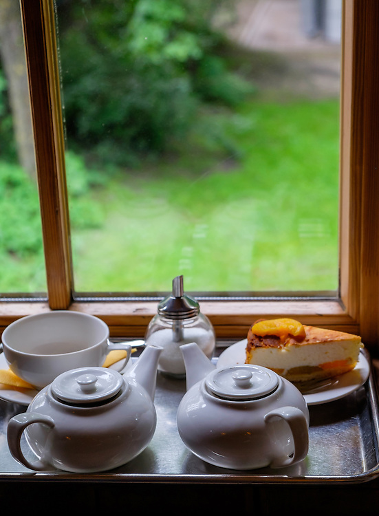 RIGA, LATVIA - CIRCA MAY 2014: Cup of tea and cake in the glass tea house in one of the parks in Riga.