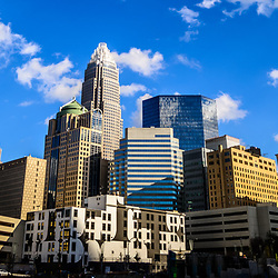 Panoramic Charlotte skyline photo with a blue sky and clouds.  Panoramic photo ratio is 1:3. Includes One Wells Fargo Center, Two Wells Fargo Center, Bank of America Corporate Center, Bank of America Plaza, 121 West Trade building, and Carillon Tower. Charlotte, North Carolina is a major city in the Eastern United States of America