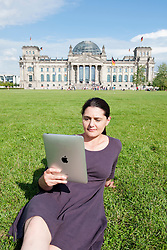 Woman relaxing and surfing the internet with an iPad outdoors in the Tiergarten near the Reichstag in Berlin Germany