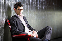 Stylish Man sitting legs crossed in metal room side view