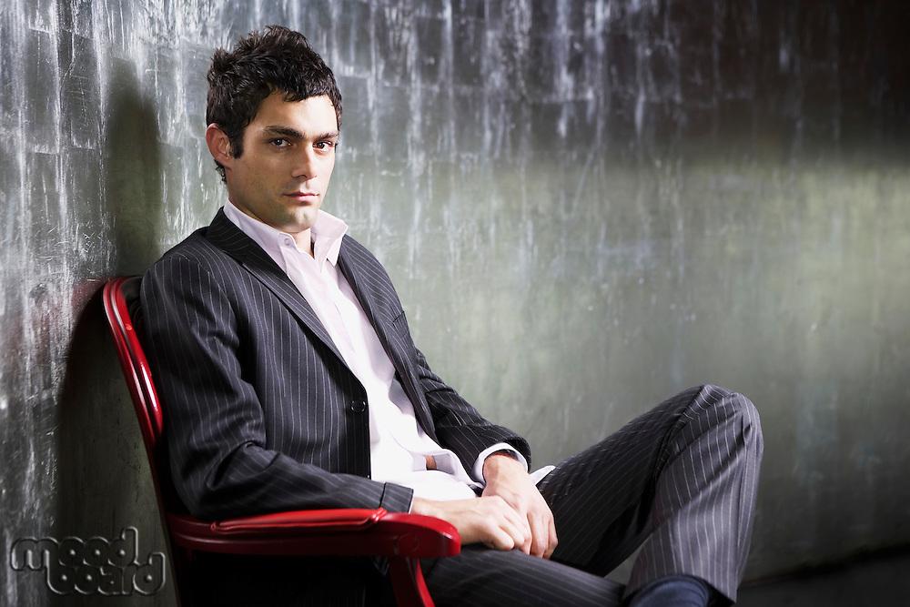 Stylish Man sitting legs crossed in metal room side view