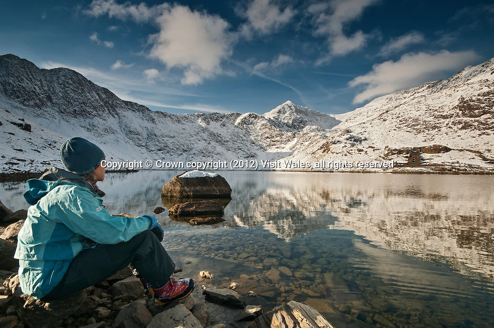Walker looking towards snow-covered summit of Snowdon (Yr Wyddfa) from Llyn Llydaw lake<br /> Winter<br /> Snowdonia<br /> Gwynedd<br /> Mountaineering<br /> Walking<br /> Activities and Sports