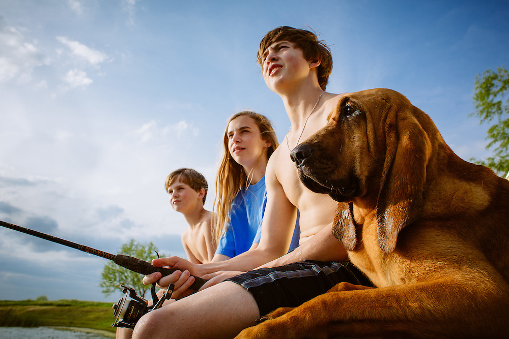 Adolescent boy fishes with his family.<br /> Country lifestyle.<br /> Photographed by editorial lifestyle photographer Nathan Lindstrom