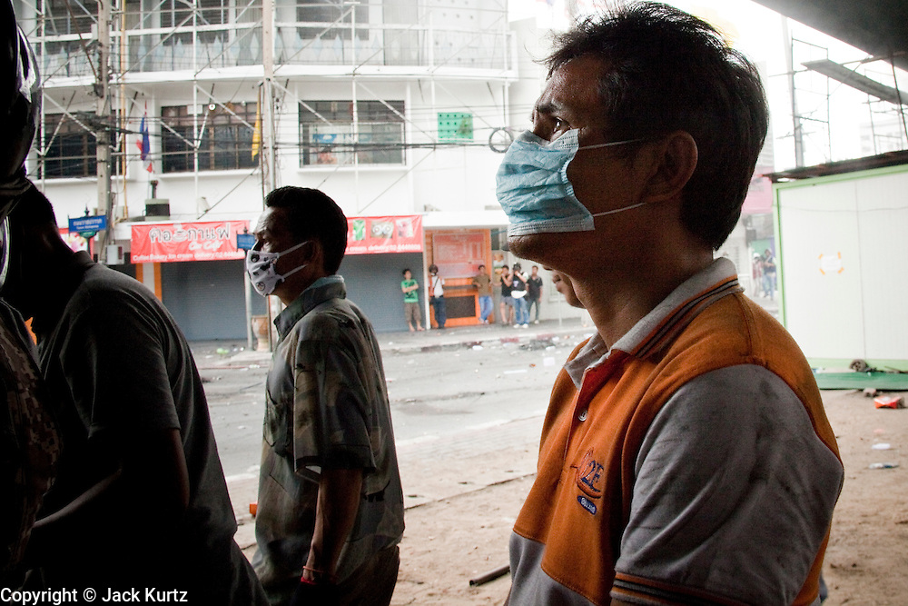 18 MAY 2010 - BANGKOK, THAILAND: A man looks for signs of snipers at Din Daeng Intersection in Bangkok Tuesday. The intersection has been under periodic sniper fire from unidentified snipers near Thai military lines. Violent unrest continued in Bangkok again Tuesday nearly a week after Thai troops started firing on protesters and Bangkok residents took to the streets in violent protest against the government. Tuesday was not as violent as previous days however. Although protesters continued to set up roadblocks and flaming tire barricades across parts of the city, there was not as much gunfire from the government lines. The most active protesters were at the Din Daeng Intersection about a mile from the Red Shirts' Ratchaprasong camp.  PHOTO BY JACK KURTZ