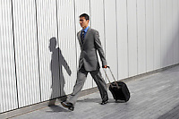 Businessman walking outdoors pulling suitcase behind him