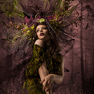 Mysterious forest goddess against a muted mauve toned forest background