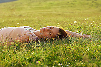 Young woman sleeping in field ground view