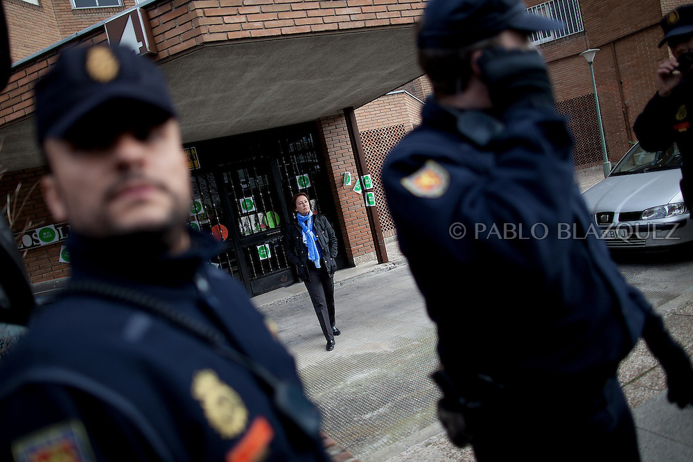 Riot police stands guard while a woman leaves the building during an 'escrache' outside the house of PP deputy Beatriz Rodriguez Salmones on April12, 2013 in Madrid, Spain. The Mortgage Holders Platform (PAH) and other anti evictions organizations have been organizing 'escraches' for several weeks under the slogan 'There are lives at risk' to claim the vote for a Popular Legislative Initiative (ILP) to stop evictions and facilitate social rent, outside Popular Party deputies' houses and offices. 'Escraches' are a form of peaceful protest that were used in Argentine in 1995 to publically denounce pardoned members of the dictatorship for their crimes at their doorsteps.