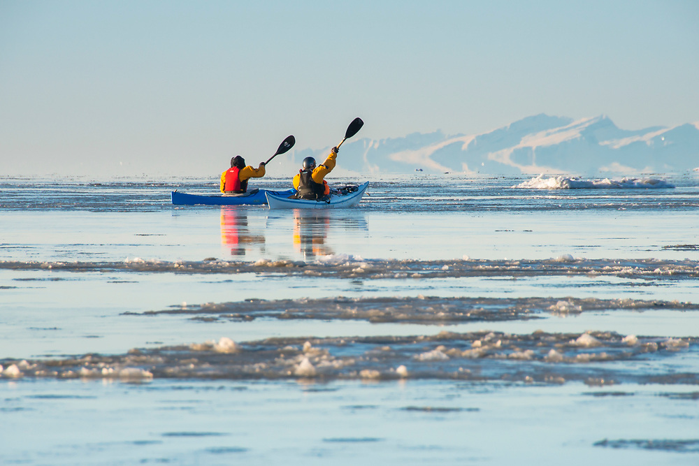 Kayakers paddle among the ice flows of Cook Inlet with Mt. Redoubt in the background. M.R.