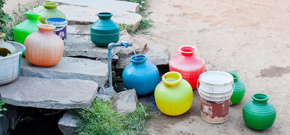 Colorful plastic containers by water fountain (India)