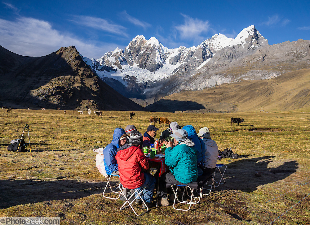 """Trekkers eat breakfast at sunny Tuctucpampa campground below Nevado Jirishanca (left, """"Icy Beak of the Hummingbird"""" 6094 m) and Rondoy (right 5870 m). Day 2 of 9 days trekking around the Cordillera Huayhuash, in the Andes Mountains, Peru, South America."""