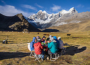 "Trekkers eat breakfast at sunny Tuctucpampa campground below Nevado Jirishanca (left, ""Icy Beak of the Hummingbird"" 6094 m) and Rondoy (right 5870 m). Day 2 of 9 days trekking around the Cordillera Huayhuash, in the Andes Mountains, Peru, South America."