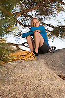 Woman climber sitting on boulder
