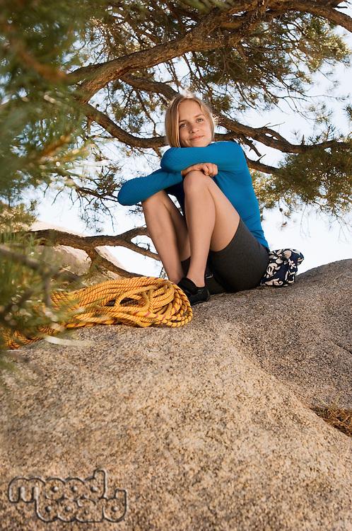 Woman climber sitting on boulder