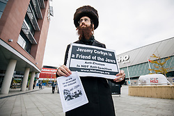 © Licensed to London News Pictures. 26/09/2018. Liverpool, UK. An Orthodox Jew holds a sign which reads 'Jeremy Corbyn is a Friend of the Jews' outside the Labour Party Conference ahead of Labour Leader Jeremy Corbyn's speech. Photo credit: Rob Pinney/LNP