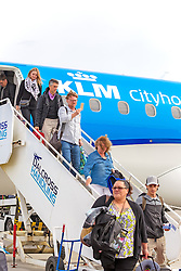 Inverness Airport welcomed KLM's Inaugural flight from Amsterdam. To celebrate the new route, the first flight from Schiphol, Amsterdam was greeted by a water cannon salute upon arrival.  On board were Barry ter Voert, Senior Vice President, Air France KLM European Markets and Wilco Swejen, Director for Aviation Marketing, Schipol Airport.  Provost Helen Carmichael, The Highland Council, Inglis Lyon, Managing Director of Highlands and Islands Aiports and Drew Hendry MP (Inverness, Nairn, Badenoch and Strathspey) met the delegation, officially welcoming the group to the Highlands. <br /> <br /> Pictured: Passengers disembark from the inaugural flight<br /> <br /> Malcolm McCurrach | EEm | Tue, 17, May, 2016