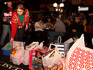 As some watch the fourth quater of the Army-Navy football game on the big screen, Rick (left) and Barb Miller of Bellbrook add to the collection of toys at the Dublin Pub, the first stop of the Santa Pub Crawl through the Historic Oregon District near downtown Dayton, Saturday, December 10, 2011.  The toys or $10 are admission for the crawl, and get picked up by Marines for the U.S. Marine Corps Toys for Tots program.