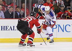 Mar 6; Newark, NJ, USA; New York Rangers center Brian Boyle (22) skates with the puck while being defended by New Jersey Devils defenseman Anton Volchenkov (28) during the first period at the Prudential Center.