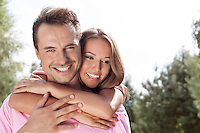 Portrait of happy young man being embrace by woman from behind in park