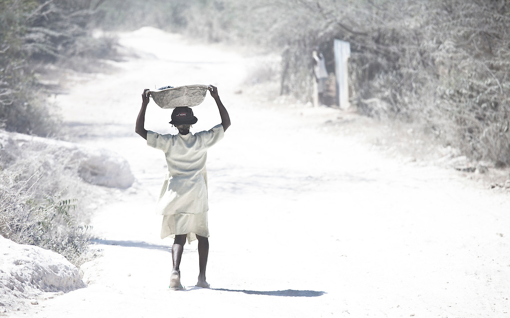 A woman carries a basin of clothes on her head down a dusty road in Anse a Galet, Ile de la Gonave, Haiti