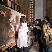 Rome, Italy, March 15th, 2018. The former church of Santa Marta al Collegio Romano.   The  restorer, Caterina Manisco, explains to the students of the 2D class of the Liceo Artistico di Via Sarandì in Rome  the process of restoration - mainly cleaning and reintegration - that is taking place on the painting detached from the Casino della morte of Palazzo Farnese depicting Narciso alla fonte, by Domenico Zampieri, known as Domenichino (1581-1641), dated between 1503-1505, which was removed from the wall in 1826. The open restoration site set up inside the former church of Santa Marta al Collegio Romano, and in the space of the former Coro delle Monache,  was conceived by the Istuituto Superiore per la Conservazione ed il Restauro of Rome to give the public the possibility of participating in the practice of a restoration site and to increase the awareness by non-specialist visitors of the importance of conservation in our artistic heritage.<br /> 