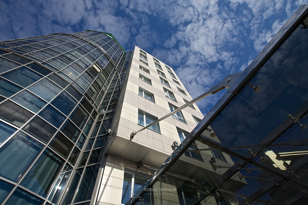 Exterior architectural view of business centre by Borodkin architects in Kyiv, Ukraine. Daylight with sunlight and sky reflections in the glass tower.