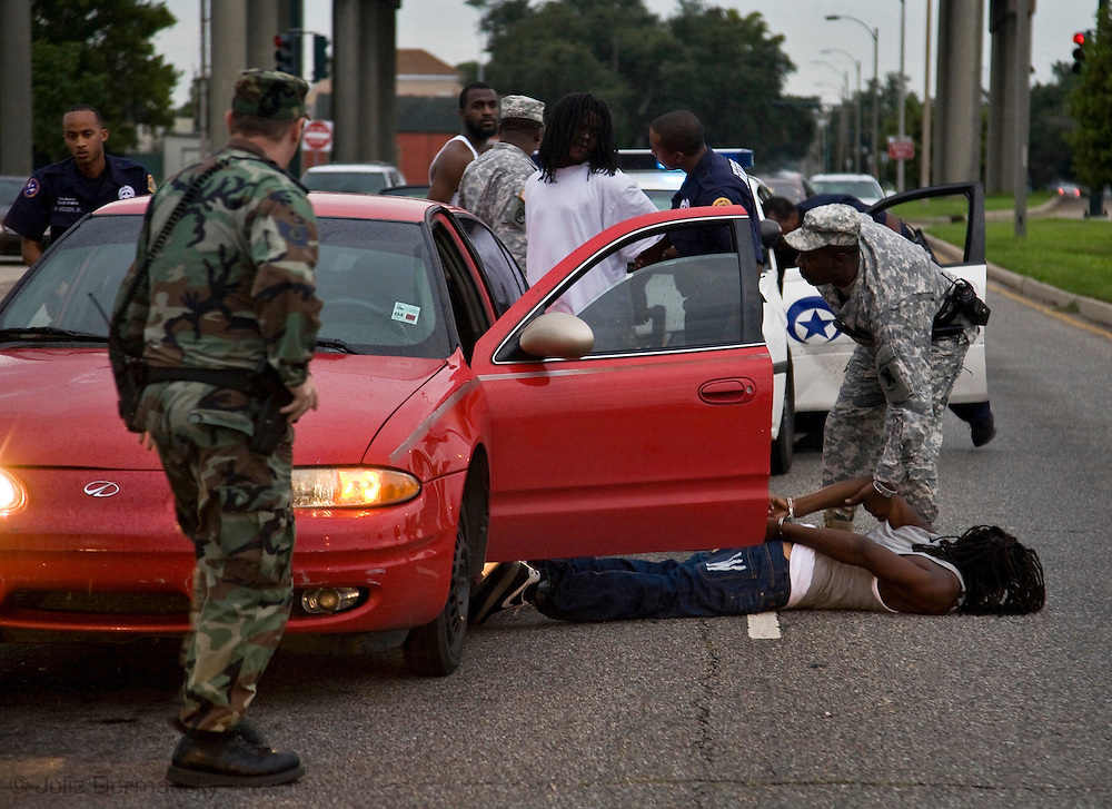 National Guard and police working together in New Olreans. This car was stopped by police  because it fit the description of a call that came in of young men firing shots out of it. The Guard helped block traffic and look for the weapons assumed to be thrown from the car. Shot While Riding along the National Guard in the 9th Ward in New Orleans.