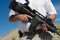 Man holding machine gun at firing range, mid section