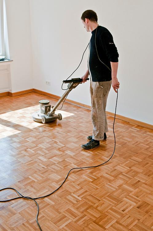 Ein Handwerker verteilt eine Ölschicht zur Versiegelung eines Parkettbodens  mit Hilfe einer Poliermaschine |  worker prepares a wooden floor  with the help of a polishing machine